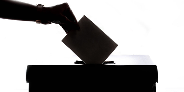 Hand Putting Envelope into Election Box